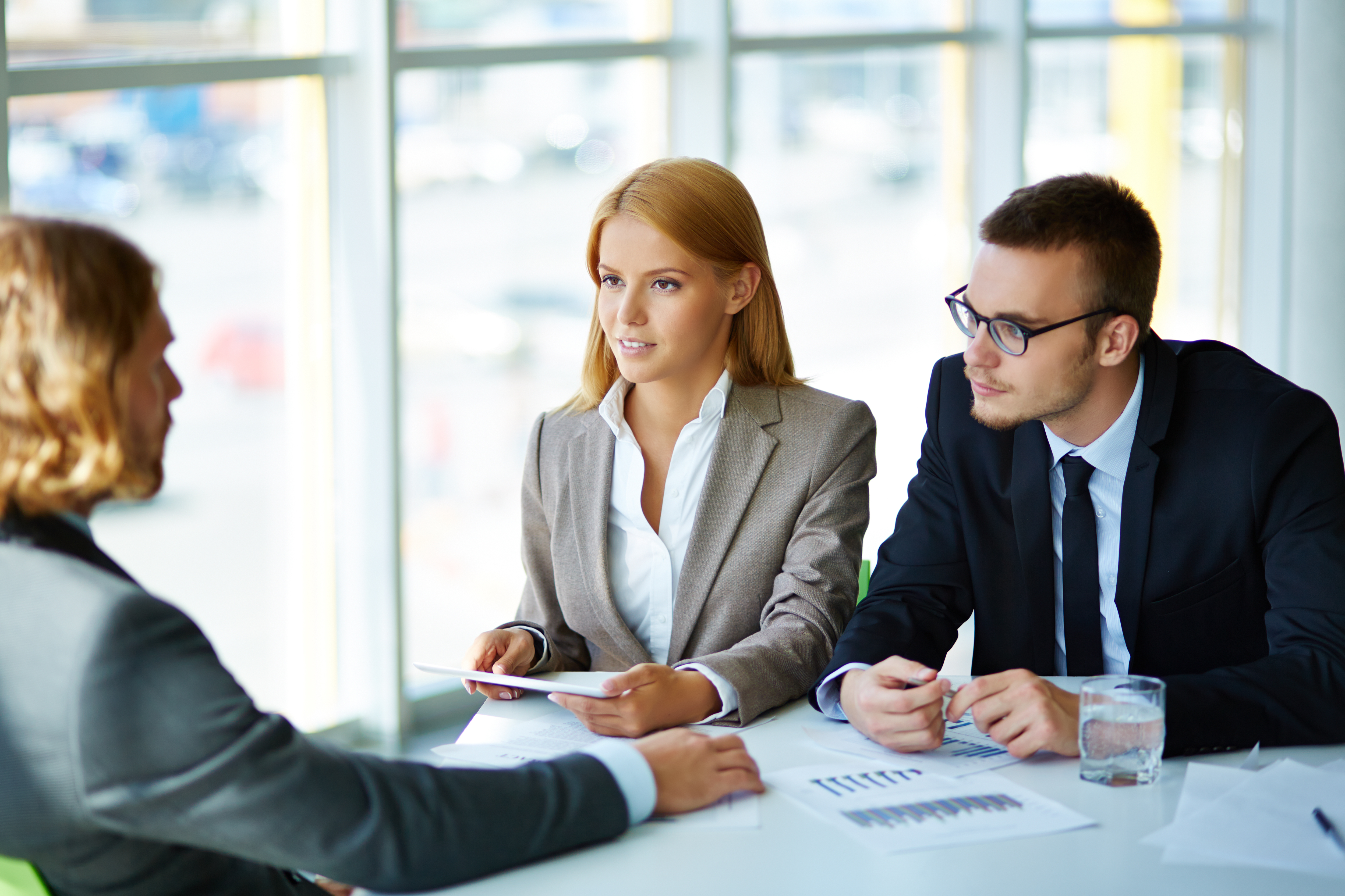 Two serious business partners listening attentively to young man at meeting in office
