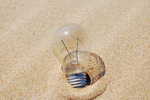 concept of a lightbulb on sand (environment issue)
